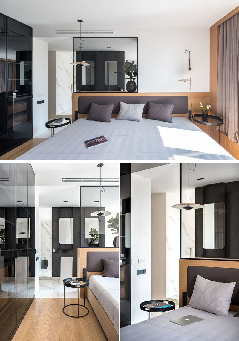 This master bedroom has a simple wood backdrop behind the bed, while transparent glass provides a view through to the ensuite bathroom. #BedroomDesign #MasterBedroom