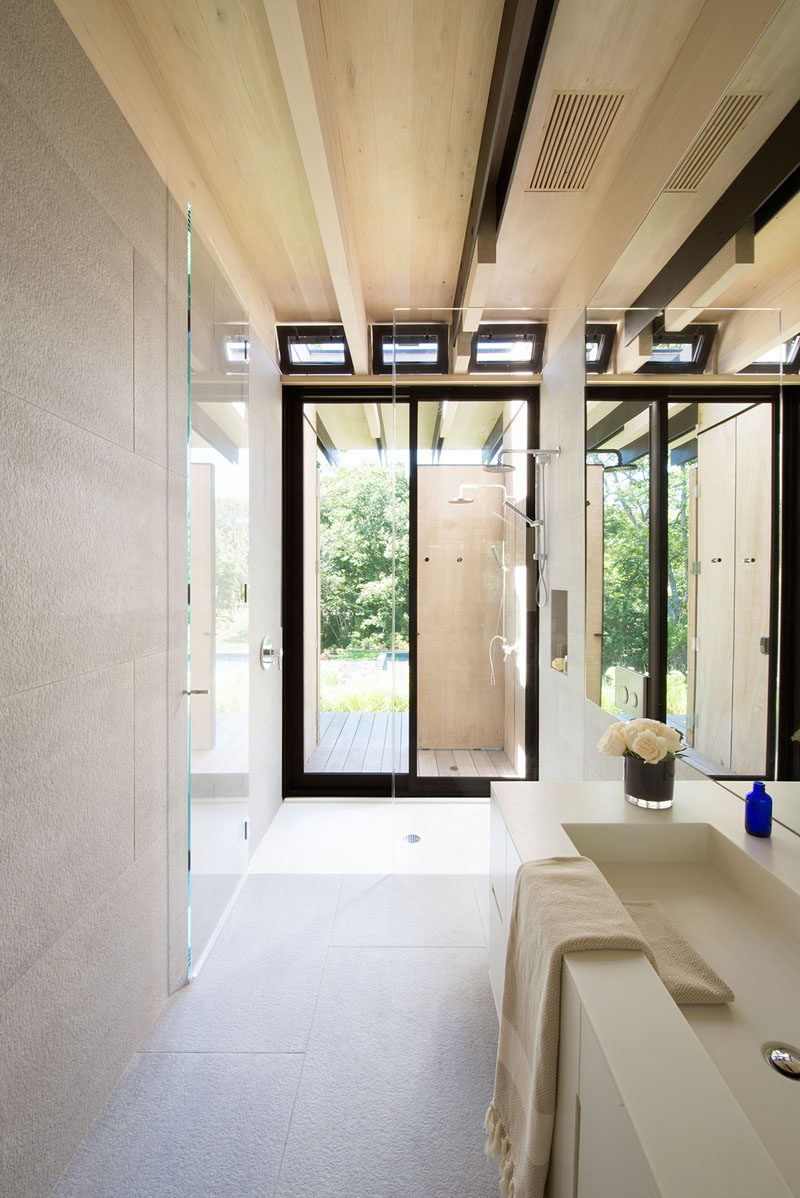 This minimalist bathroom has two showers, one indoors and one outside. #OutdoorShower #BathroomDesign