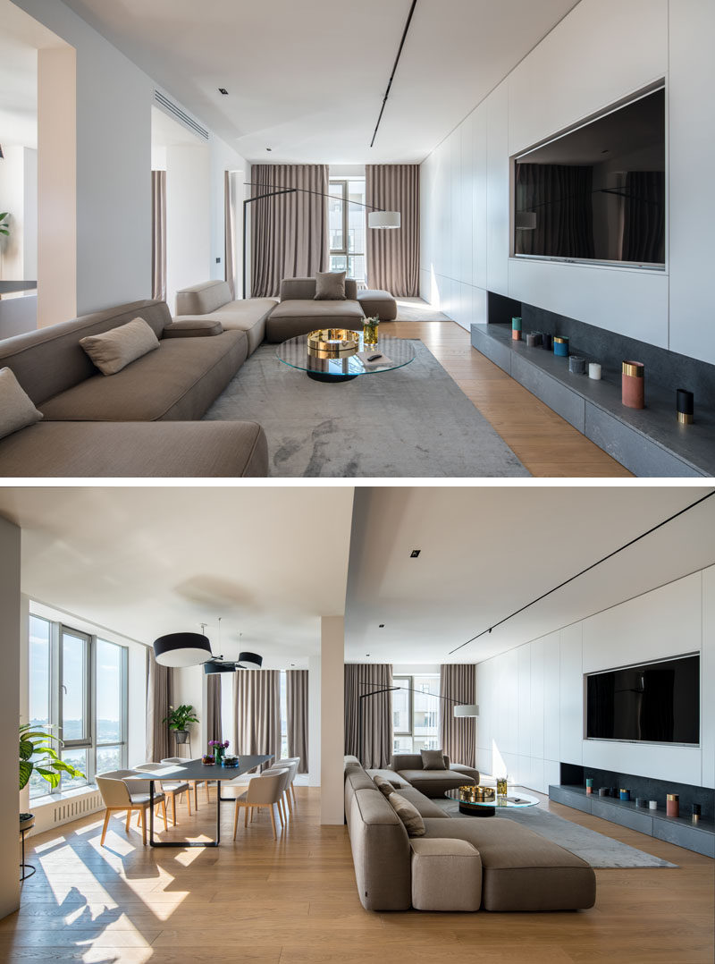 This open living area is long, with the couches focused on the television, and a window at the end of the room adds natural light to the space. #LivingRoom #InteriorDesign #ModernLivingRoom