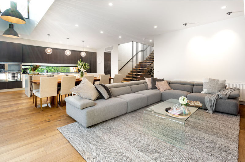 Inside this modern house, the main social areas are all located in a large single room, that features a vaulted ceiling. #ModernInteriorDesign #LivingRoom