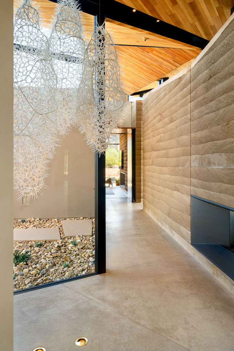 Materials such as layered walls of rammed-earth, wood, metal, and concrete, have been used throughout the design of this modern house. #Concrete #Wood #RammedEarth #Architecture