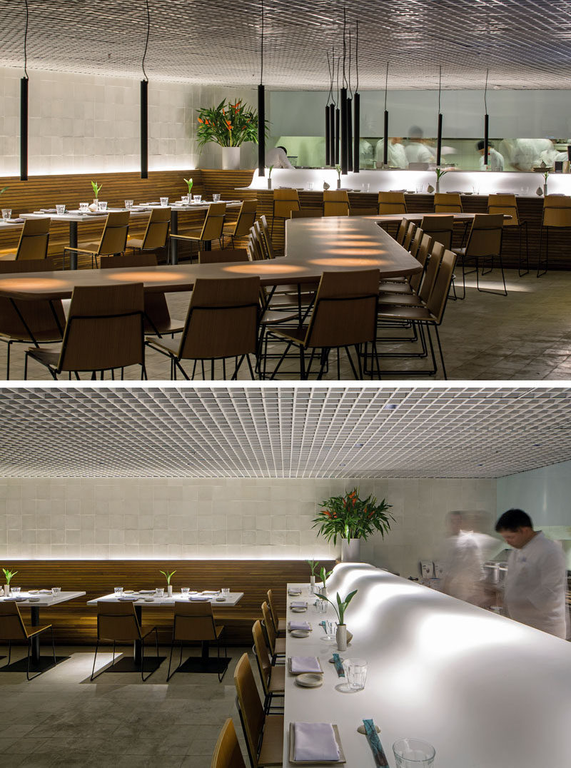 This modern restaurant features smooth Corian countertops, wood slat benches and a custom communal table. #RestaurantDesign #ModernRestaurant #InteriorDesign