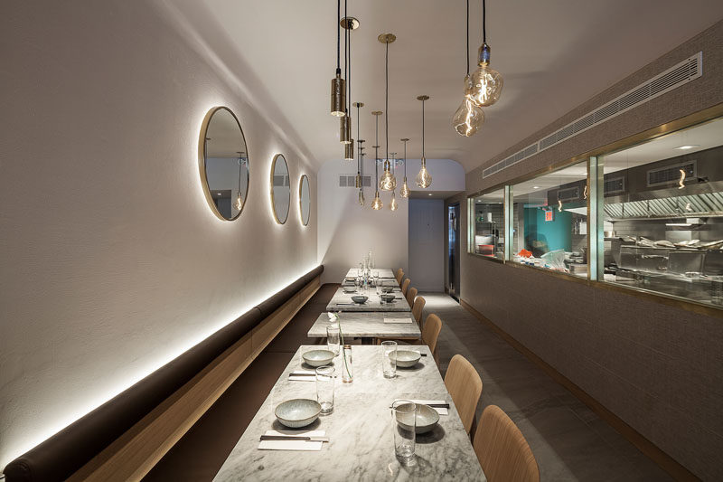 At the rear of this modern restaurant, white walls are highlighted by hidden lighting behind the banquette and the mirrors. #Restaurant #RestaurantDesign