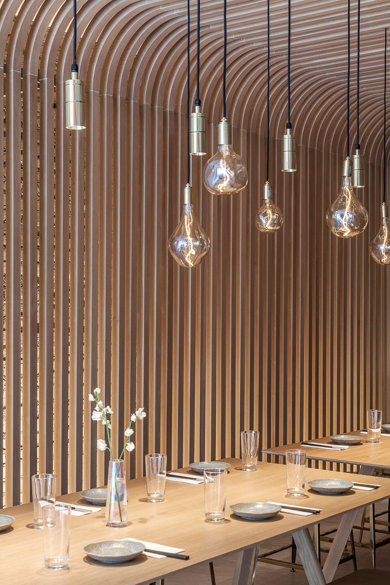 Lining the walls and ceiling is a wood slat screen that resembling the rice noodle featured in this modern restaurant. #WoodSlats #WoodScreen #Restaurant #RestaurantDesign #Interiors
