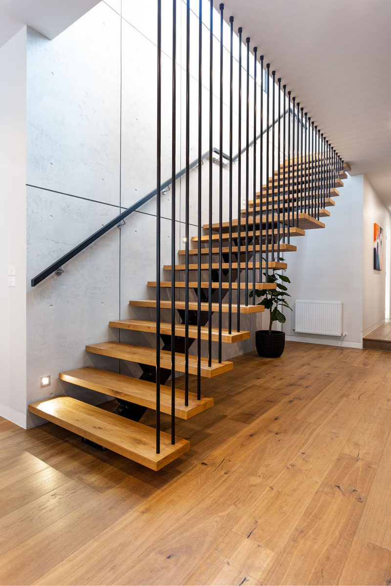 This modern open tread staircase has wood treads and a single metal stringer. #Stairs #ModernStairs #StaircaseDesign
