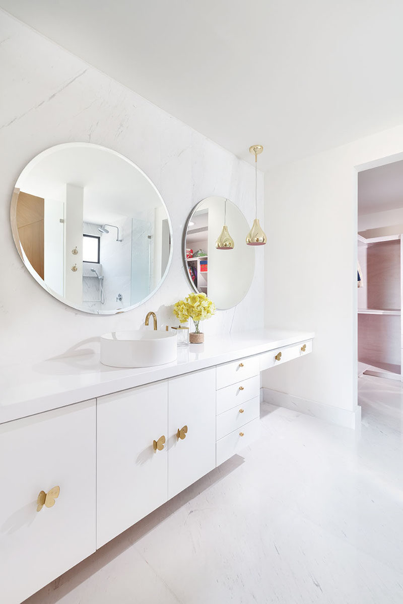 This modern white bathroom has large round mirrors, a long white vanity and a make-up area. #ModernBathroom #WhiteBathroom