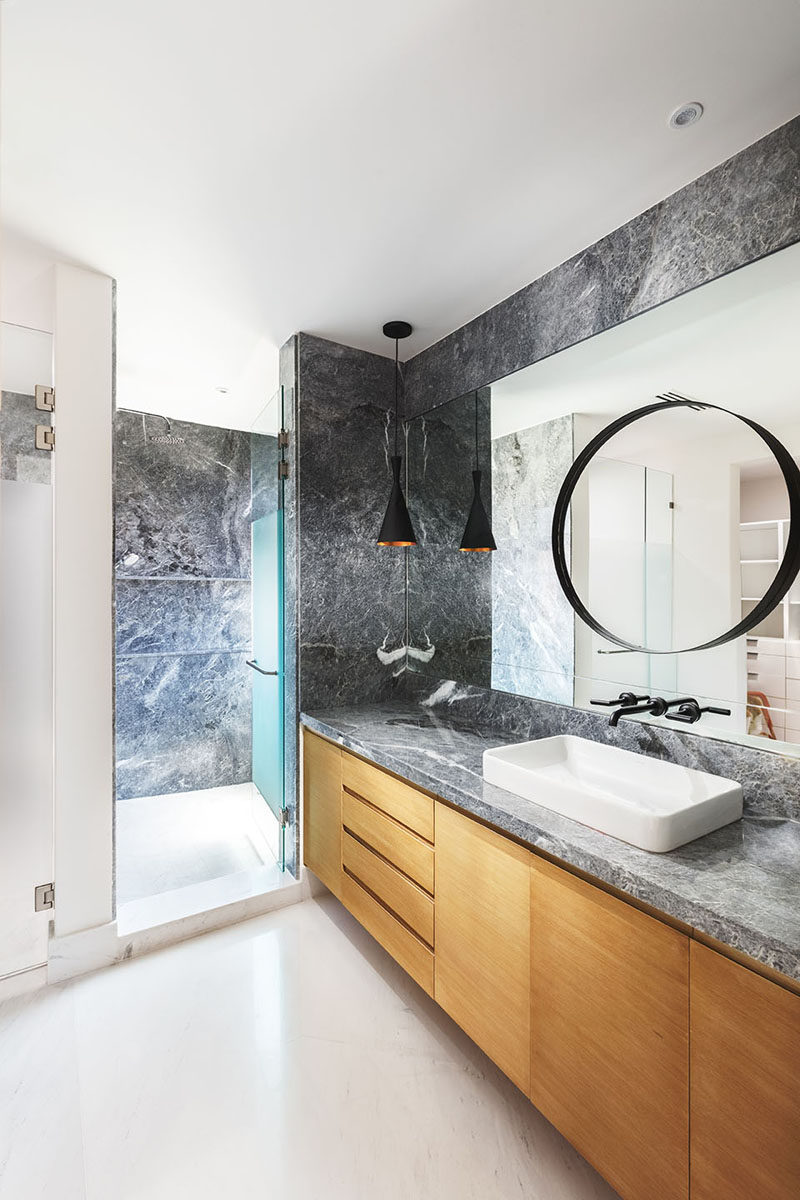In this modern ensuite bathroom, grey stone covers the walls and is used for the counter on top of the light wood vanity. #GreyAndWoodBathroom #BathroomDesign #ModernBathroom