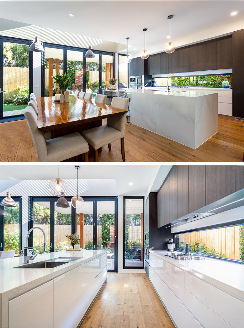 This modern kitchen has a long horizontal window that looks out to the garden at the side of the house, while the dark wood cabinets contrast the light island and lower cabinets. #ModernKitchen #KitchenDesign