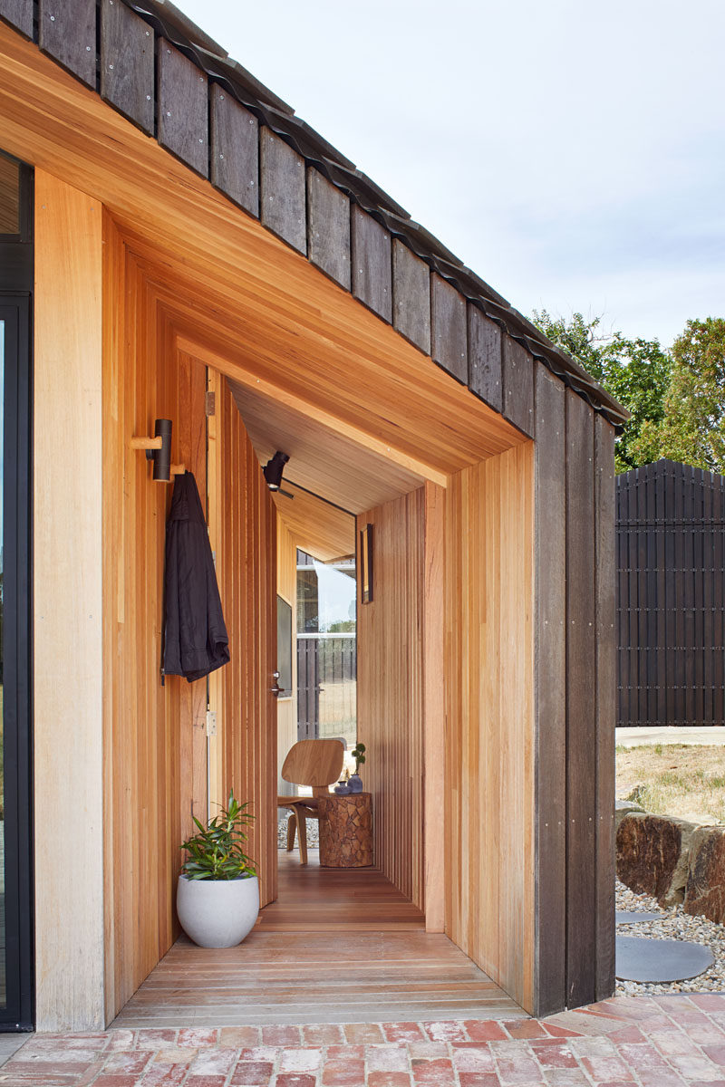 The exterior of this modern house addition is clad in spotted gum decking boards that have been stained black, enhancing the resemblance of the dilapidated shearing sheds. #FrontDoor #Wood #Architecture #WoodSiding