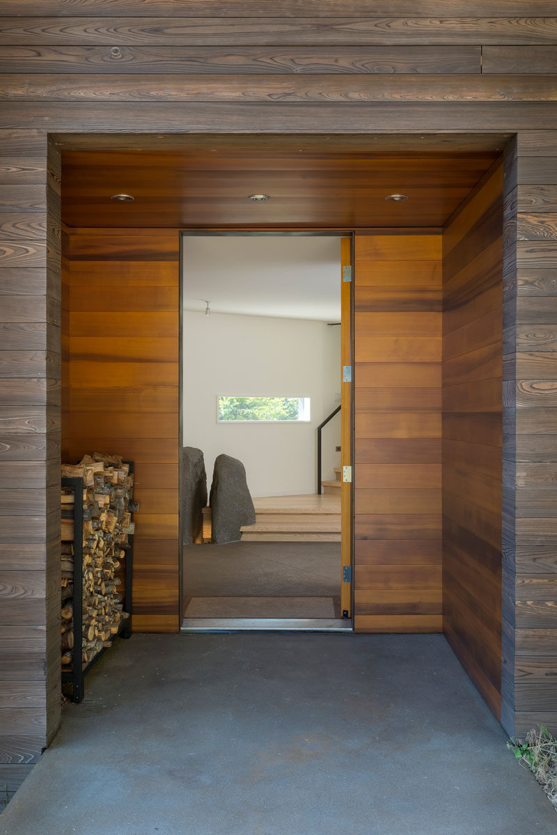The wooden front door of this modern is set back from the facade, and the alcove provides a place to keep firewood dry. #Entryway #FrontDoor #FirewoodStorage