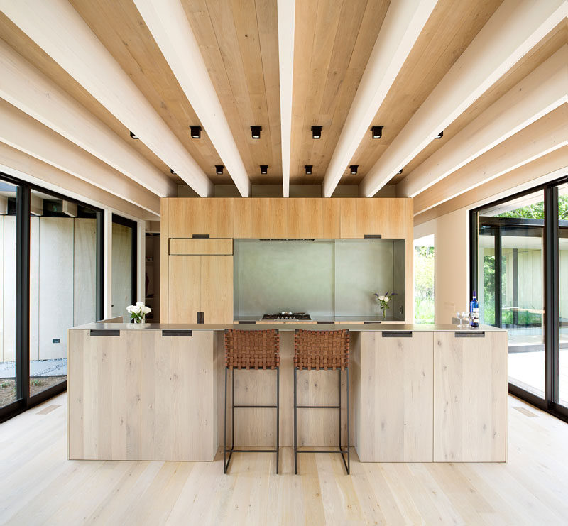 This minimalist kitchen features wood cabinets that match the wood used in the construction of the house, while a large island creates additional storage, and a place for a couple of people to sit at. #KitchenDesign #ModernKitchen #WoodKitchen