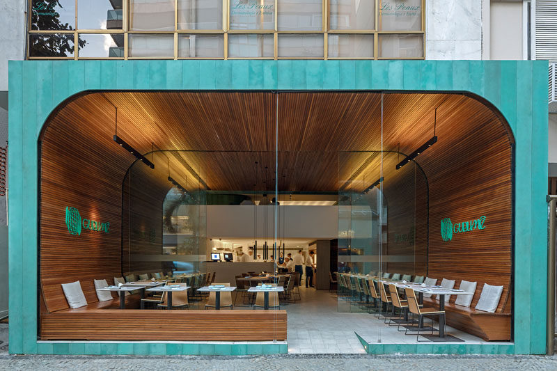 Bernardes Arquitetura have designed Gurumê, an open and modern Japanese restaurant, that features a 'tunnel' of wood slats and a facade of oxidized copper. #RestaurantDesign #ModernRestaurant #InteriorDesign