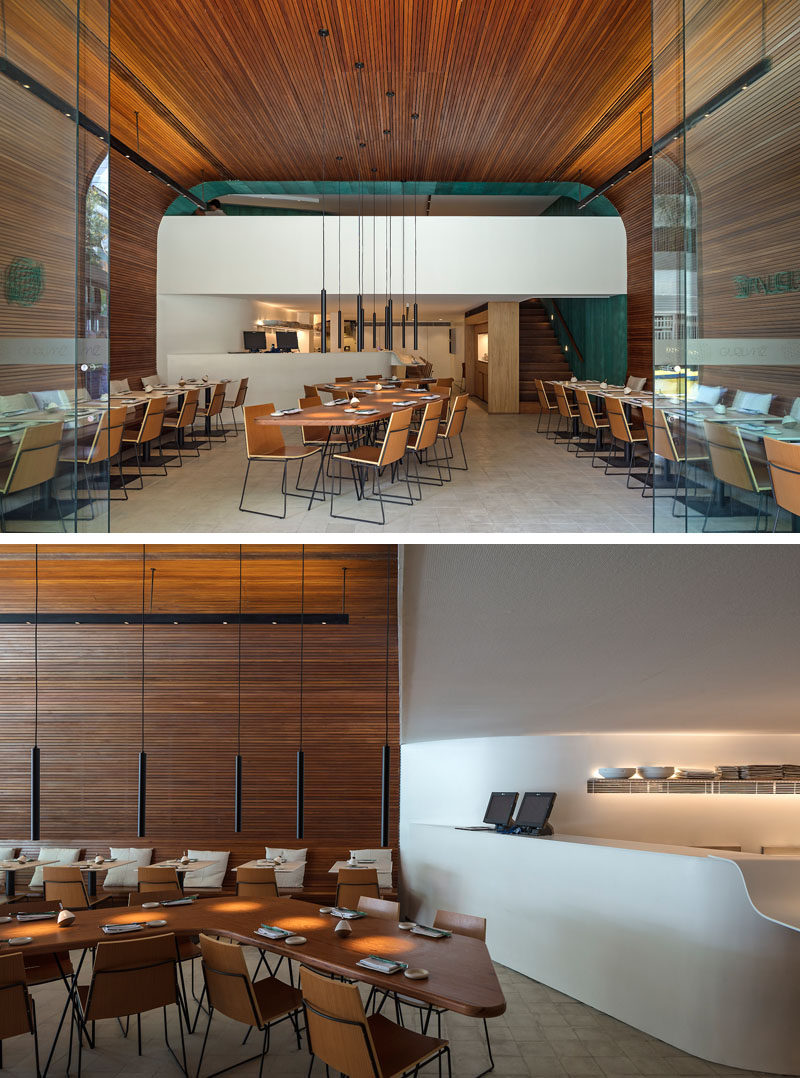 The main room of this modern restaurant is a large and vaulted space that's covered in wood slats. #WoodSlats #RestaurantDesign #InteriorDesign #ModernRestaurant