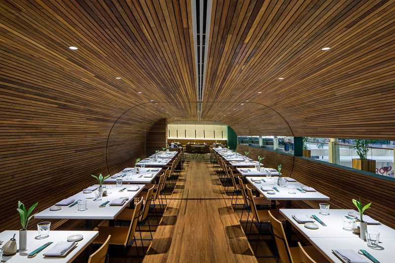 This modern restaurant has dining room lined with wood slats, creating a tunnel like appearance. #RestaurantDesign #RestaurantInterior #ModernRestaurant #InteriorDesign