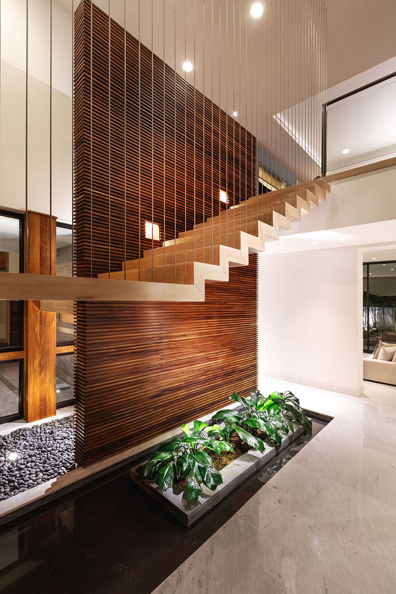 This modern staircase runs alongside a wood slat wall made from Parota. A touch of nature has been included underneath the stairs in the form of a water feature and planters. #WoodSlatWall #ModernStairs #StairDesign #InteriorWaterFeature