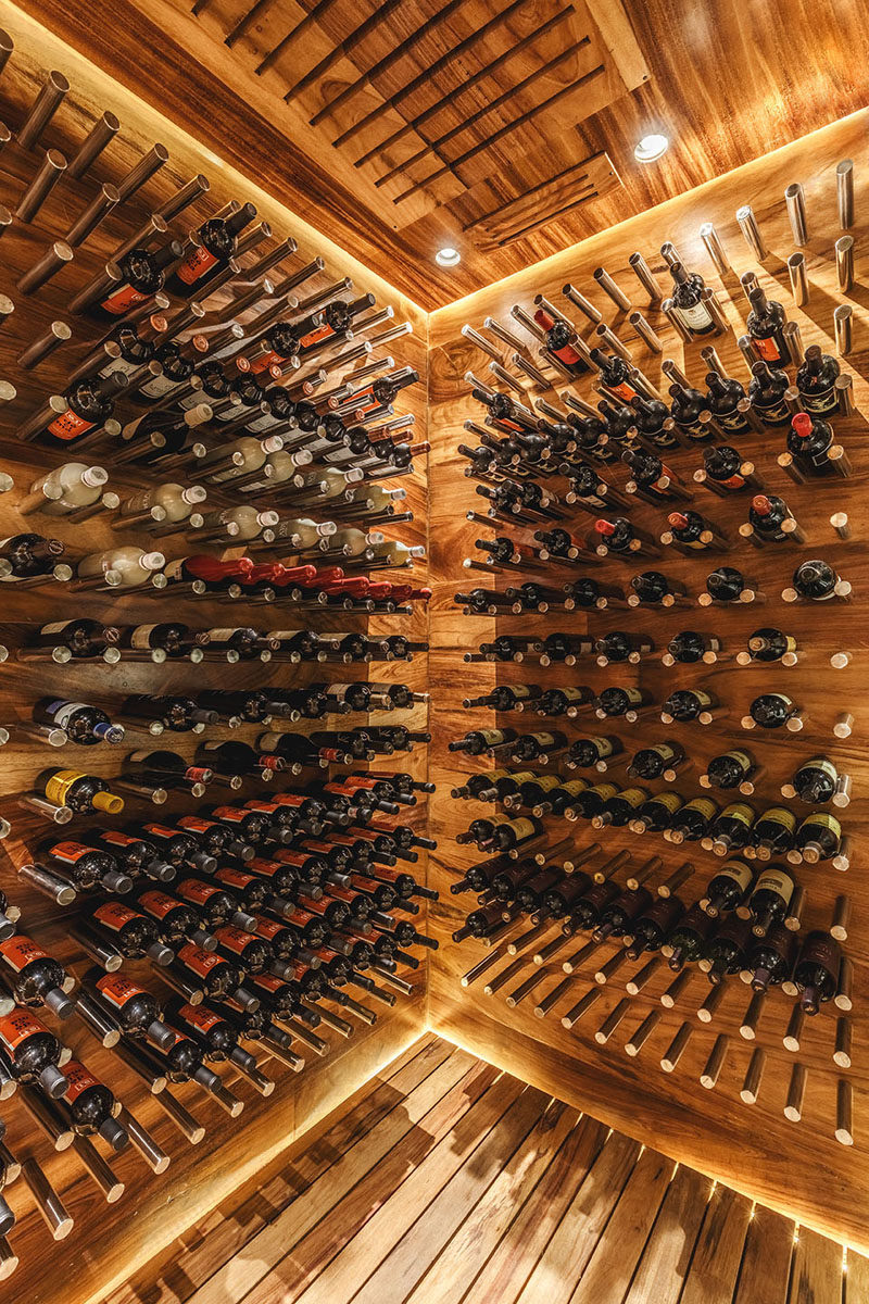This modern wood covered wine cellar uses metal rods to create exposed shelving for the wine, showing off the home owners collection. #WineCellar #WineStorage