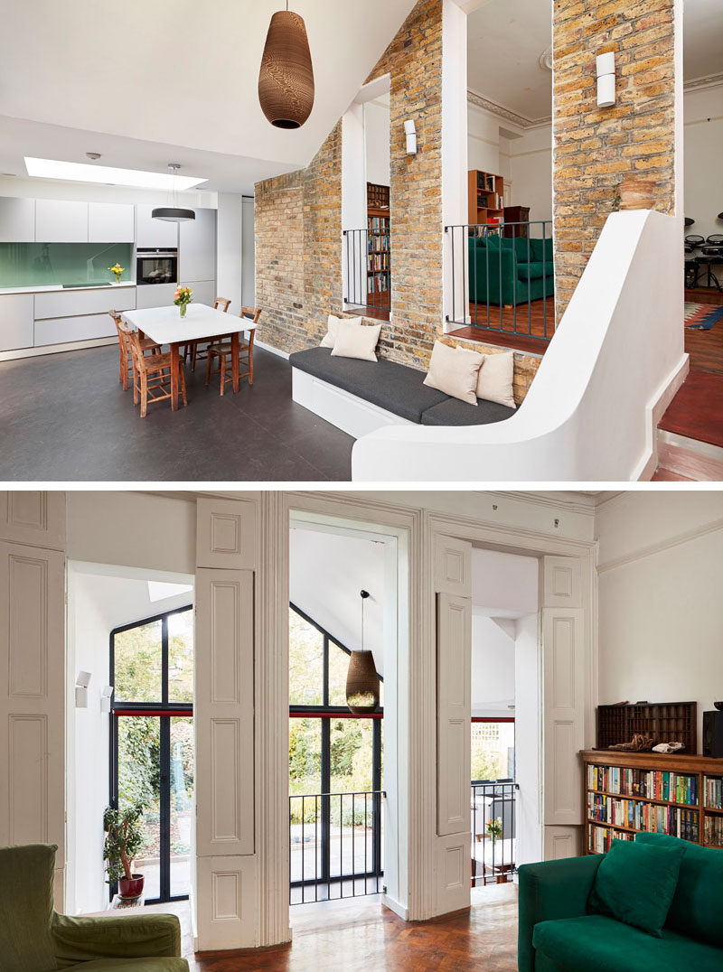 The original living room in this old Victorian home, now looks over the newly added living and dining space below. #BrickWall #ModernAddition