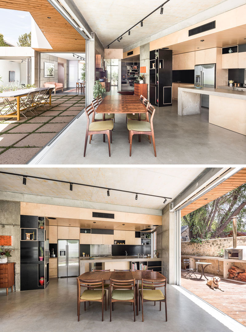 This house has an indoor/outdoor living environment, and in the kitchen, light wood cabinets have been combined with a concrete peninsula for a modern look. #Concrete #KitchenDesign #ModernKitchen #IndoorOutdoor