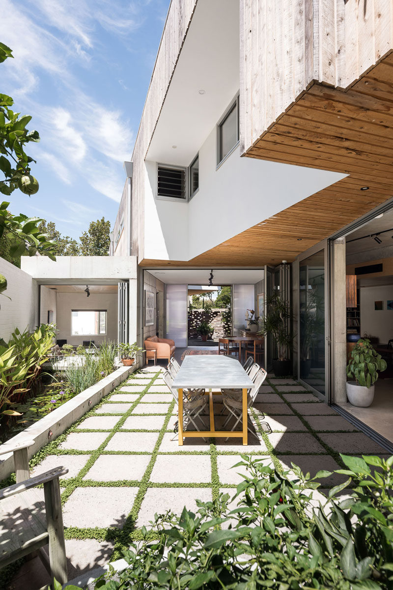 Large glass doors fold open to create an indoor / outdoor living environment for this modern house. #Patio #Pavers #Landscaping #Architecture