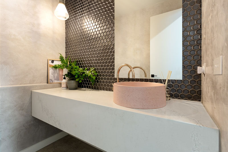 In this modern powder room, dark hexagonal tiles cover the wall, while a dusty pink round basin sits on a floating white vanity. #PowderRoom #Bathroom