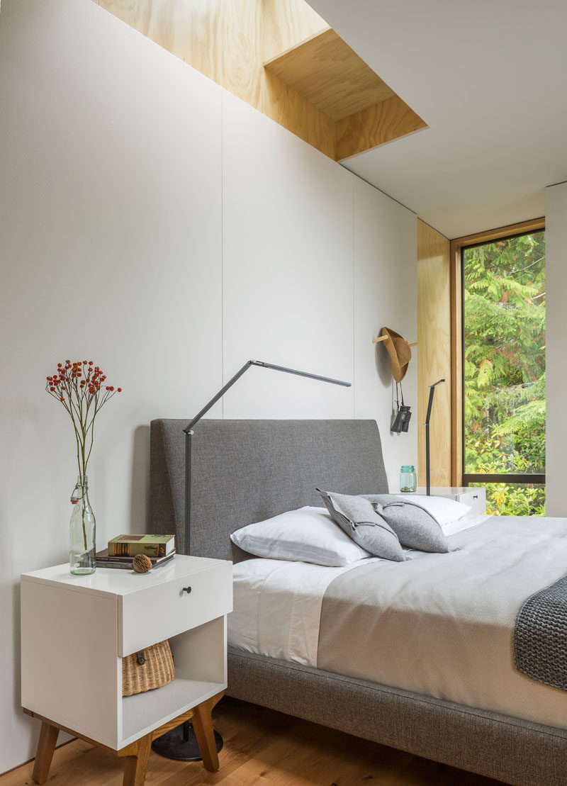 In this simple and modern bedroom, a skylight is positioned above the bed, adding natural light to the already bright white space. #BedroomDesign #ModernBedroom #Skylight