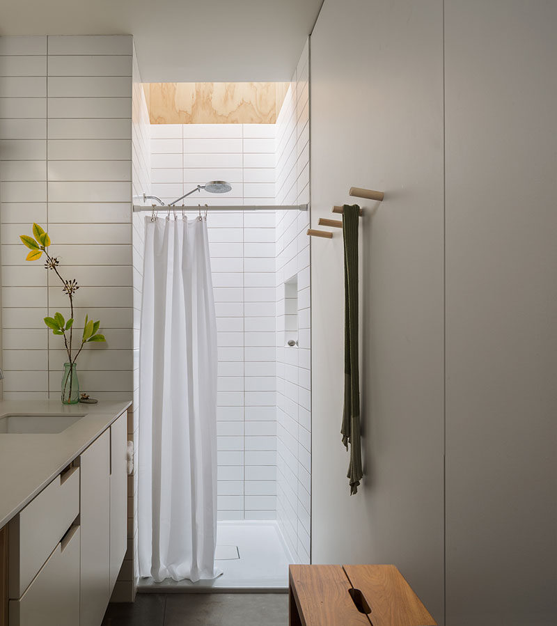 This modern and small bathroom has a skylight above the show, while long rectangular white tiles line the shower and wrap around to the vanity area. #BathroomDesign #BathroomSkylight #SmallBathroom #WhiteBathroom
