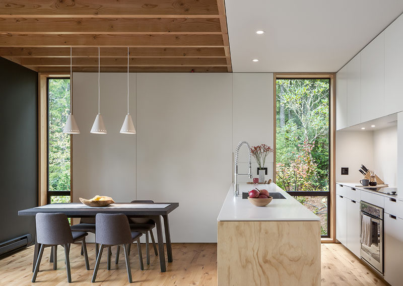 Keeping the kitchen white helps to reflect the natural light throughout the interior, and three simple pendant lights highlight the dining area. #WhiteKitchen #BrightKitchen #KitchenDesign