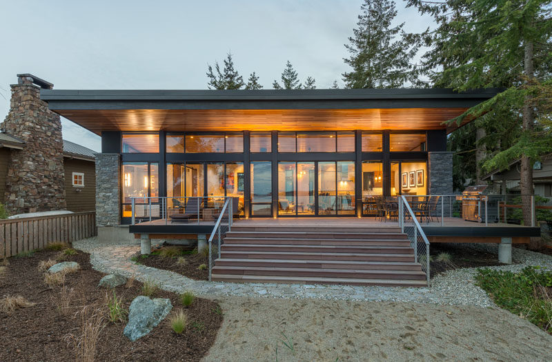 The ceiling of this modern waterfront cottage continues from the inside to the outside, creating a shaded deck for outdoor dining and relaxing. #Architecture #ModernCottage #Roof #WoodCeiling