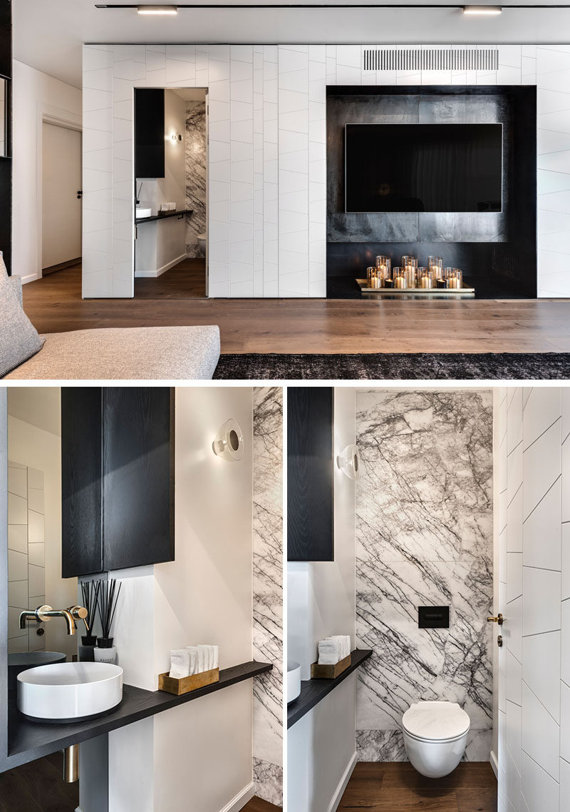 This small powder room has grey and white marble that lines the back wall, while a simple black wood vanity fits against the adjacent wall. #PowderRoom #ModernInterior #SmallBathroom