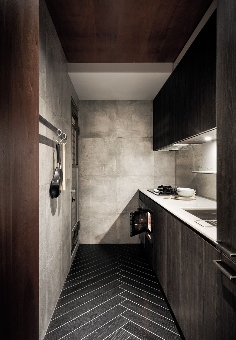In this small kitchen, rich wood elements have been combined with large format tiles on the walls and herringbone patterned flooring. #SmallKitchen #KitchenDesign #HerringboneFloor #InteriorDesign