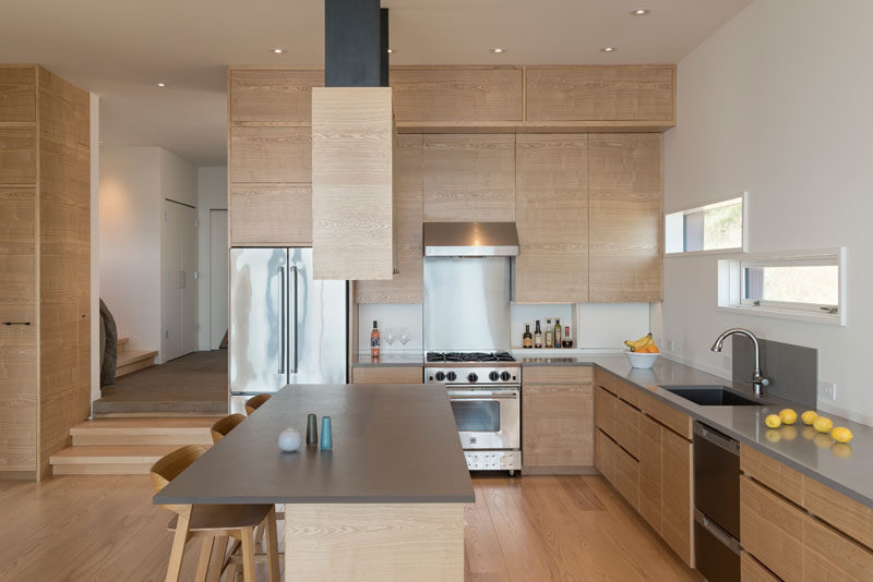 This kitchen combines wood cabinetry with a grey countertop, for a simple and contemporary appearance. #KitchenDesign #WoodKitchen
