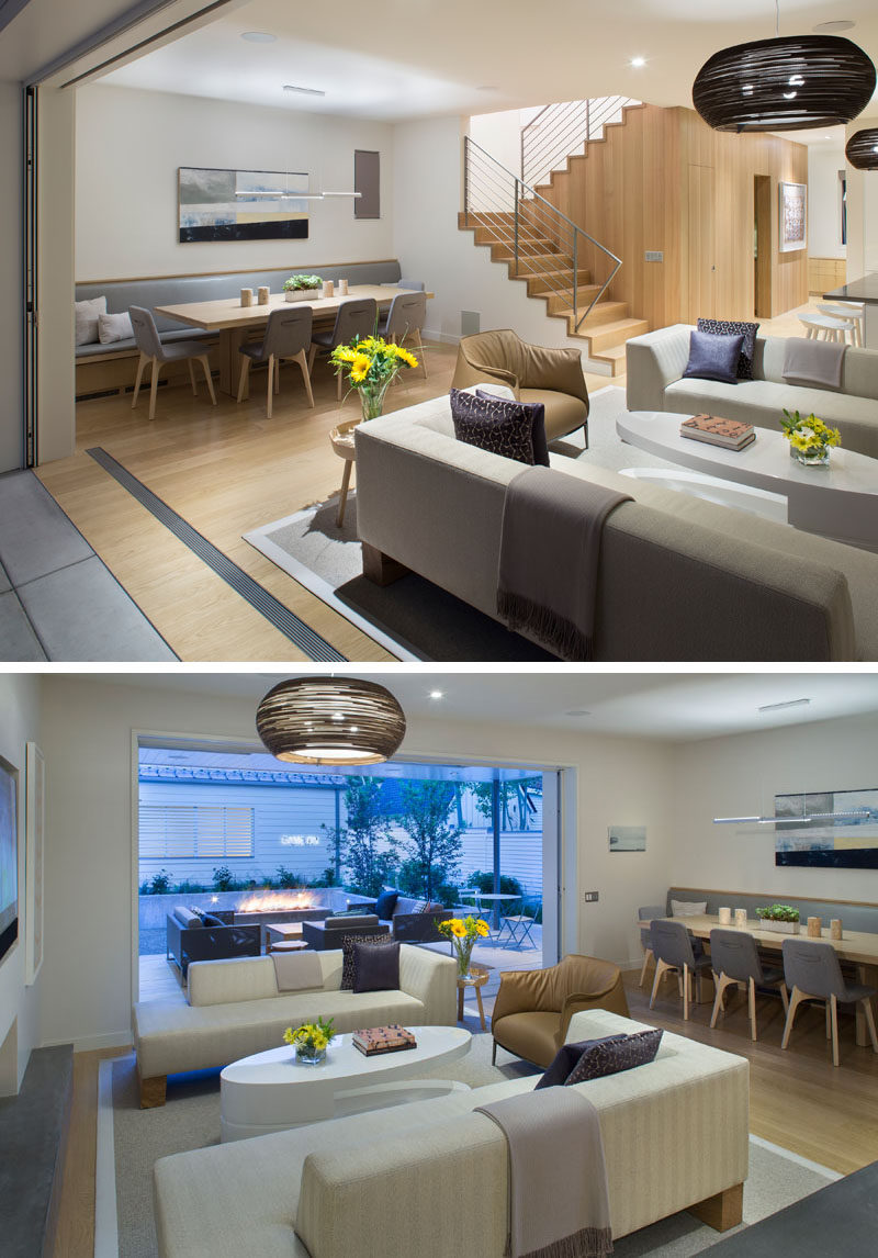Behind the living room in this modern interior is the dining area, with a built-in banquette bench that runs the length of the wall.Connecting the indoor and outdoor spaces are seamless lift and slide pocket doors. #OpenPlanInterior #Banquette #DiningRoom #LivingRoom