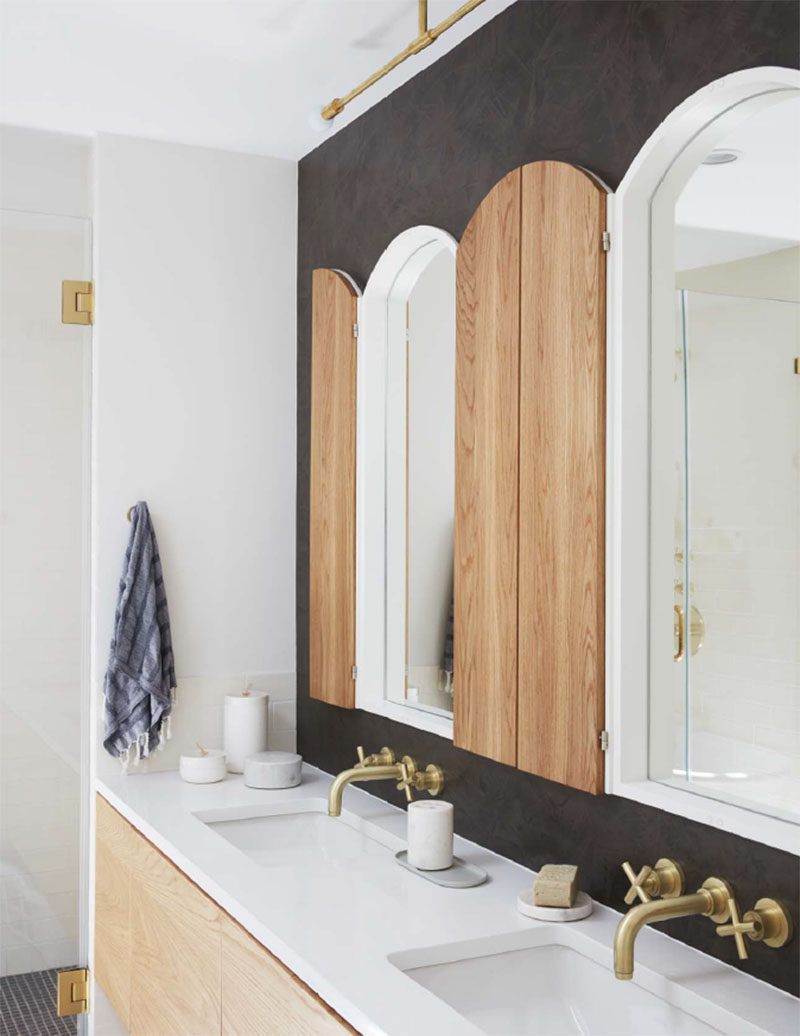 In this contemporary bathroom, a dark accent wall contrasts the white and light wood of the mirrors and the vanity. #Bathroom #ContemporaryBathroom #BathroomDesign