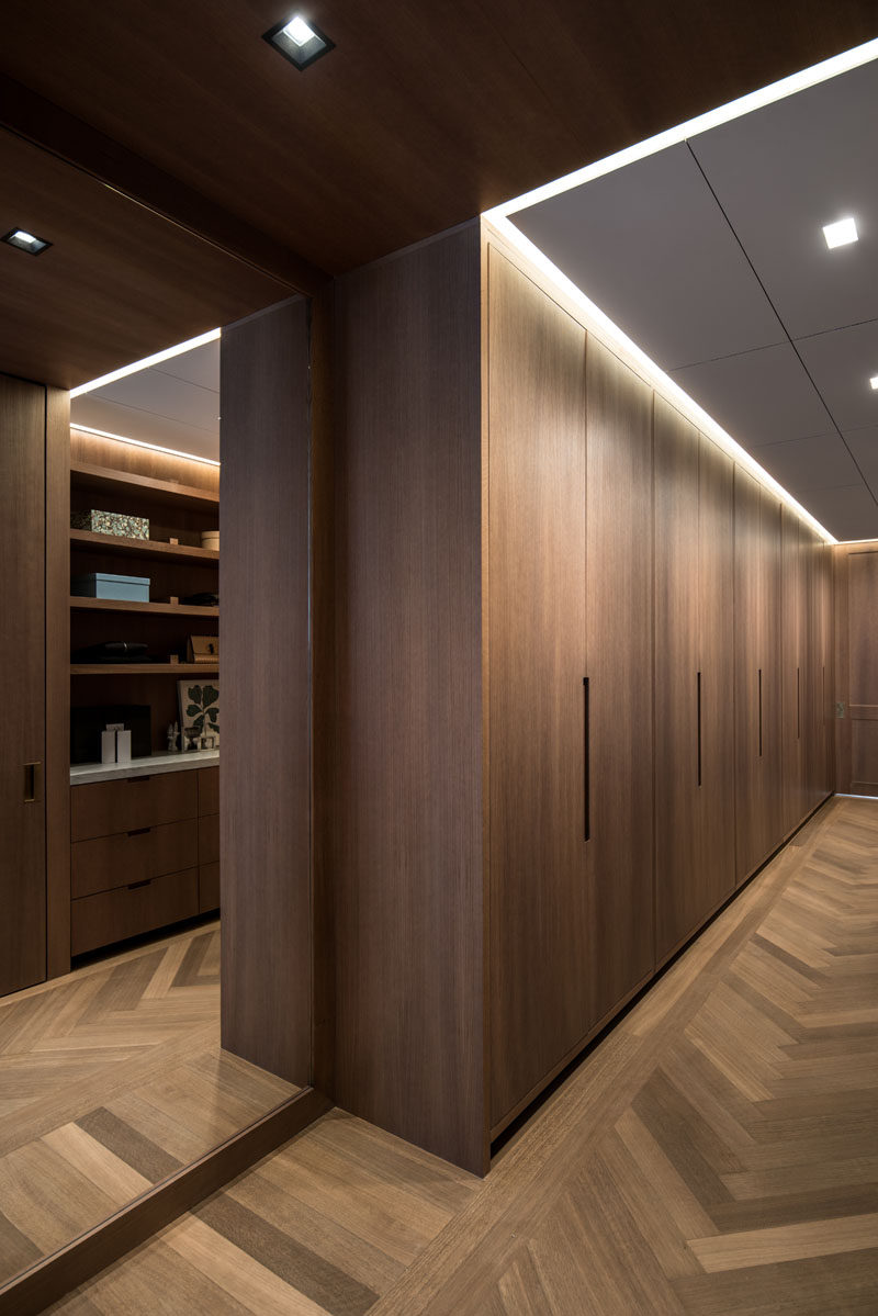 This modern walk-in closet has minimalist oak paneling and doors, and a floor to ceiling mirror reflects the light throughout the space. #Closets #InteriorDesign #WoodFlooring