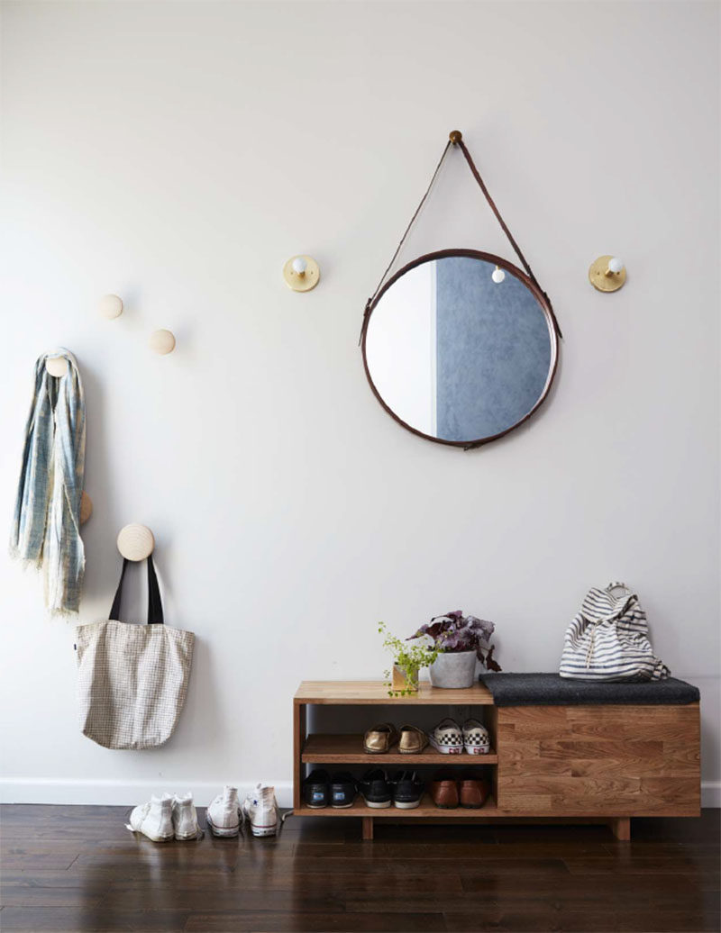 In this contemporary entryway, a round mirror is flanked by sconces, while round hooks provide a place to hang jackets and bag, and a wood bench allows to storage of shoes. #Entryway #InteriorDesign