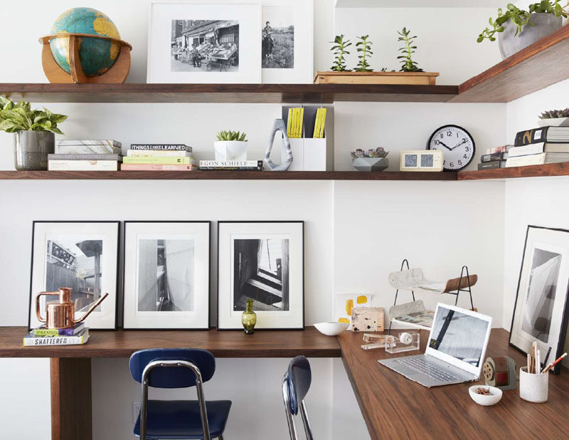 In this modern home office, wood shelves wrap around the corner of the room, while a matching desk provides enough space for two people to work. #HomeOffice #WoodShelves #Shelving #Desk