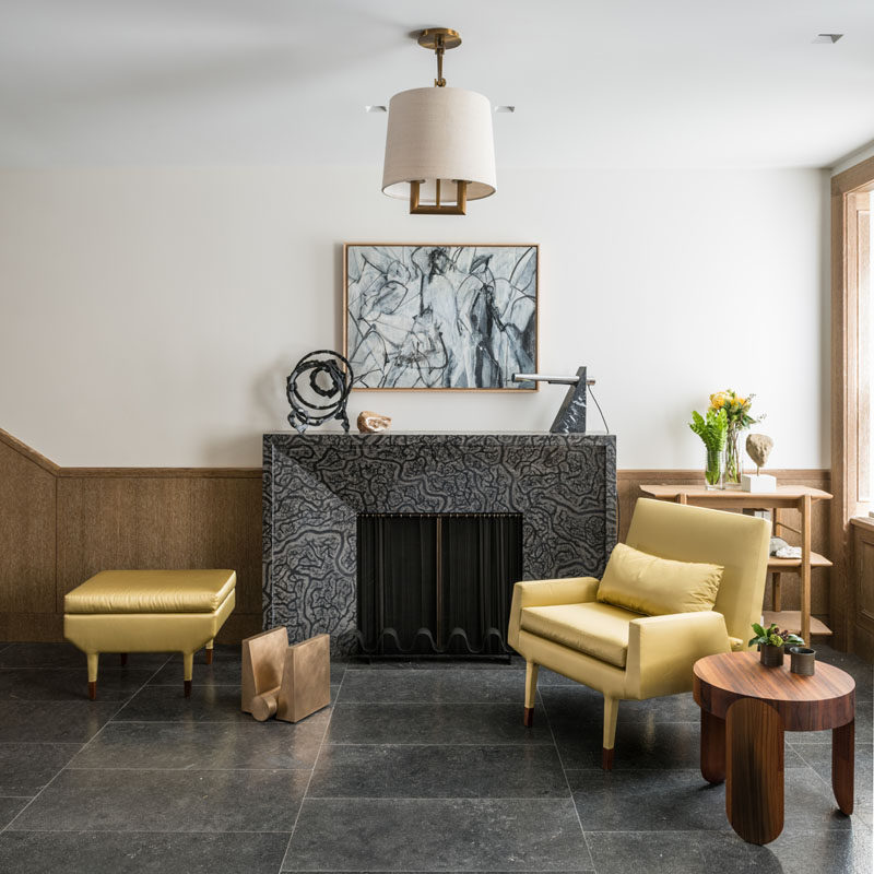 In this contemporary foyer, there's a simple sitting area next to a fireplace. Windows that look out onto the street, fill the space with natural light. #SittingRoom #Foyer #Fireplace