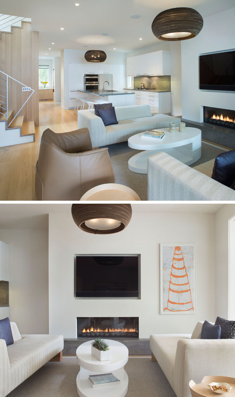This contemporary house has open floor plan that allows the mostly white kitchen to flow into the living room, that features a built-in fireplace. #WhiteKitchen #OpenFloorPlan #LivingRoom #Fireplace