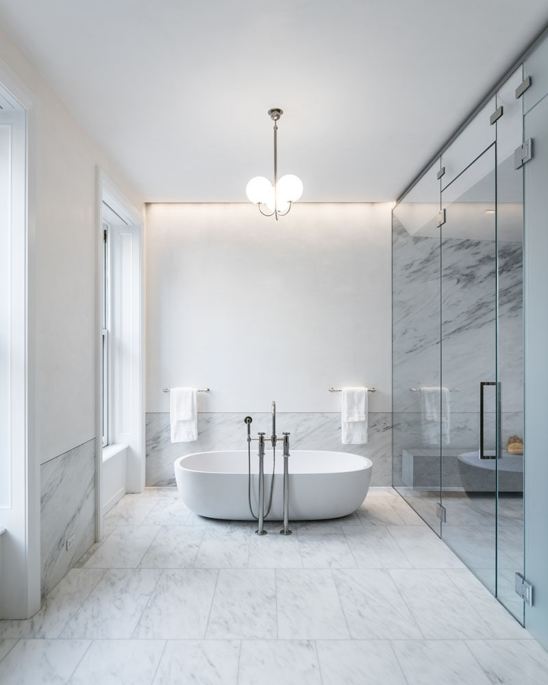 In this modern bathroom, a soaking tub by Boffi is outfitted with Waterworks taps, while a pendant light by Michael Anastassiades, hangs above it. #Bathroom #ModernBathroom #BathroomDesign