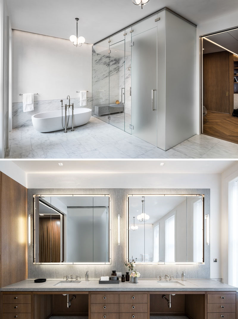 This modern master bath is clad in imperial Danby marble and white Venetian plaster. Clear glass surrounds the shower, while opaque glass houses the toilet. #ModernBathroom #MasterBathroom #Marble #Vanity