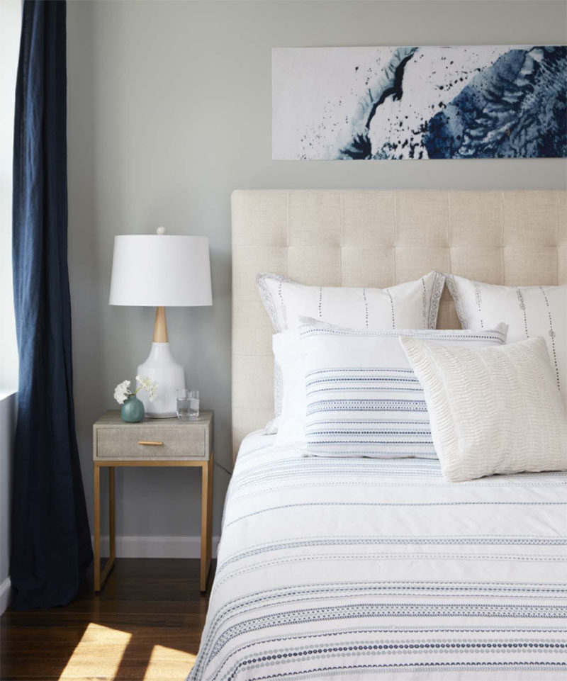 In this contemporary master bedroom, neutral tones with dark blue accents have been used to create a relaxing atmosphere. #MasterBedroom #BedroomDesign #NeutralBedroom