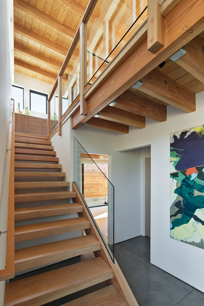 Wood open tread stairs in this modern house lead to the living spaces on the top floor. #Stairs #WoodStairs #OpenTreadStairs