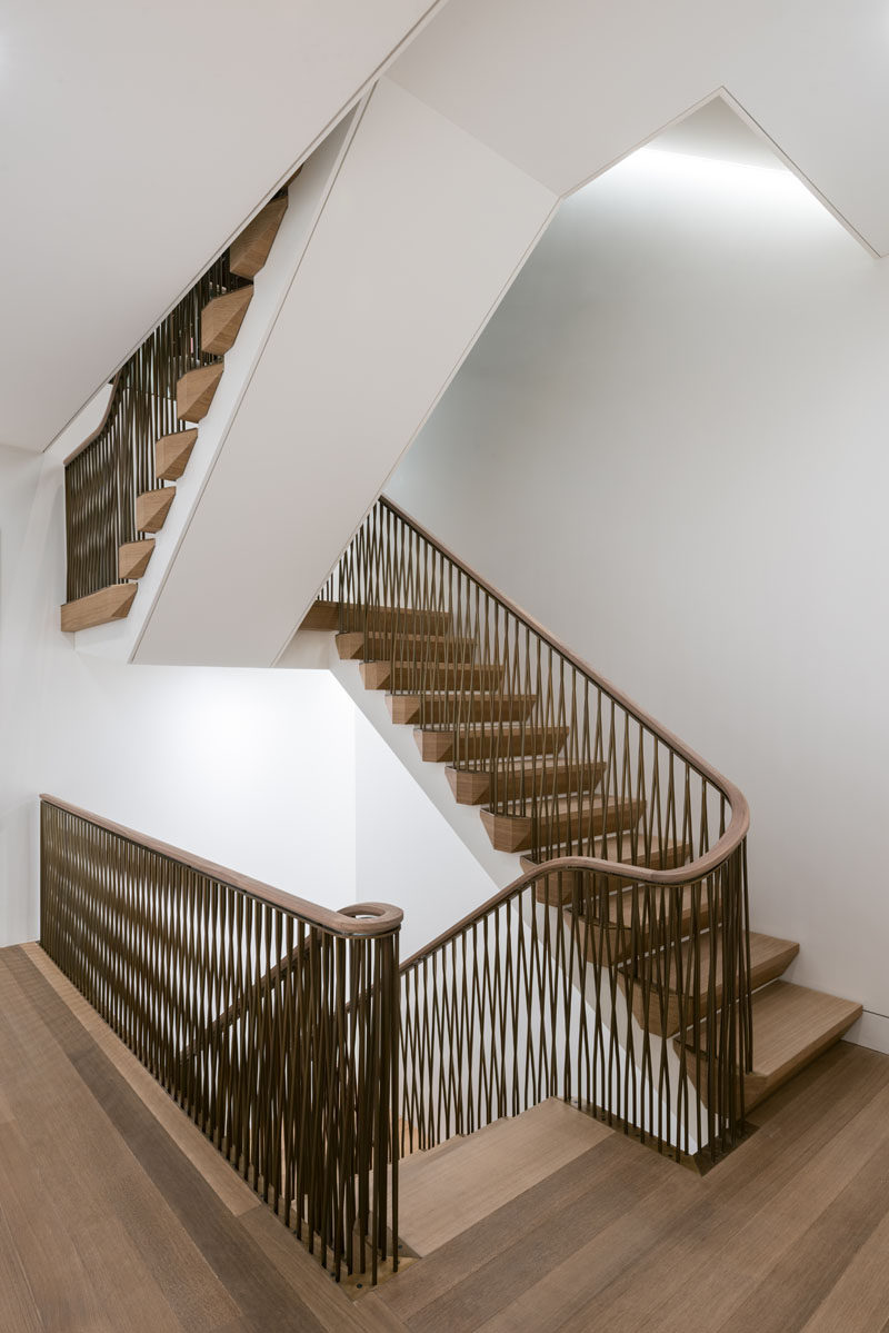 These modern wood stairs have an undulating and braided bronze railing. #Railings #BronzeRailings #Stairs