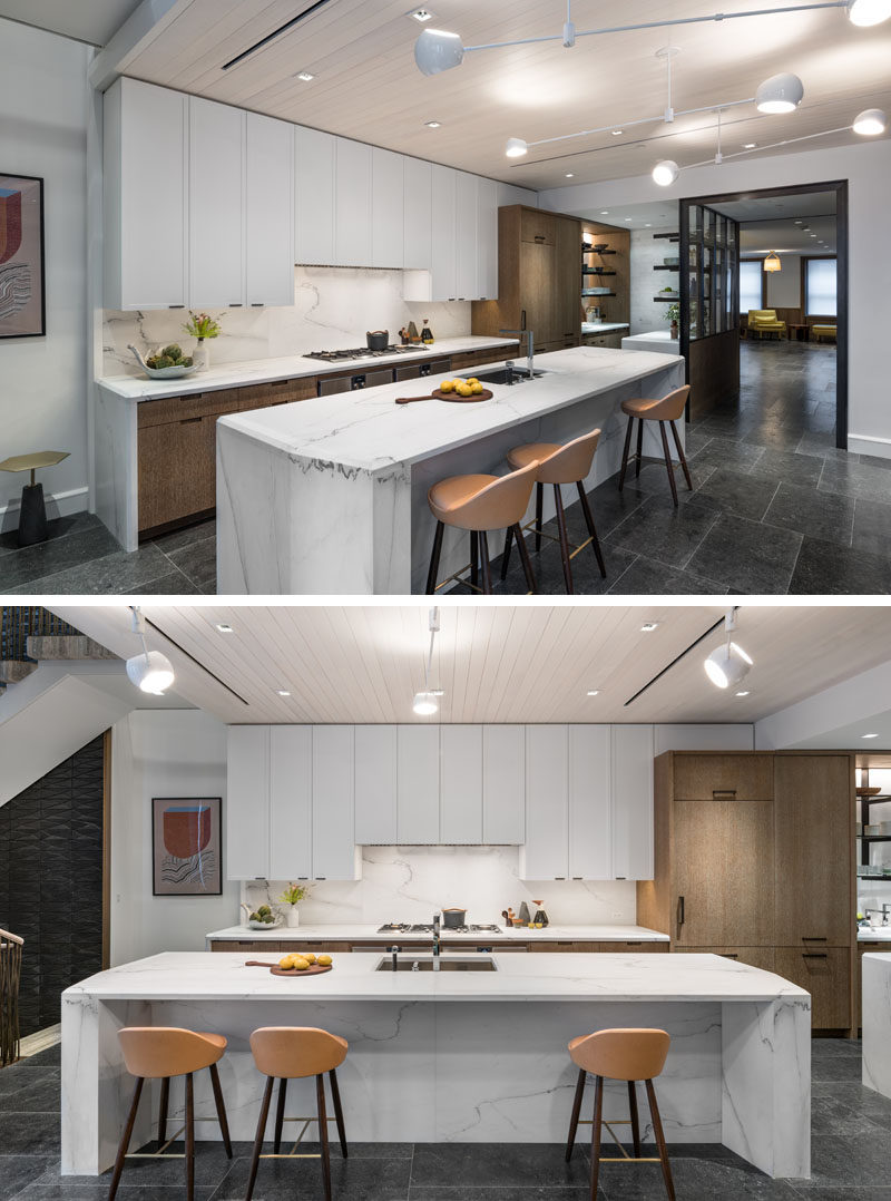 In this modern kitchen, the large island has accompanying Vintage Danish stools in vegetable tannedleather from Wyeth, while the white cabinets have been paired with wood for a contemporary appearance. #Kitchen #ModernKitchen #KitchenDesign