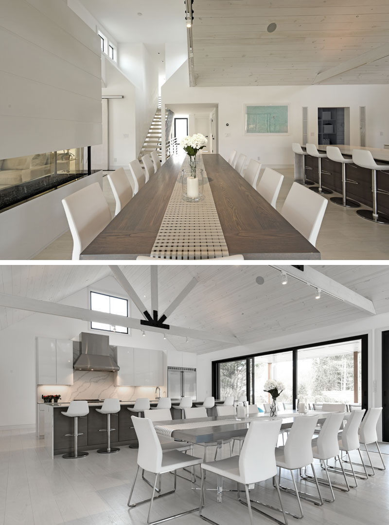 The entryway of this modern barn-inspired house opens up to a large open plan room, with the dining area and a fireplace separating the kitchen and living room. #DiningRoom #ModernDining #InteriorDesign