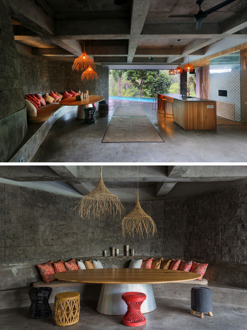 This modern house has a cave-like lounge and bar area that leads to the swimming pool. The lounge features a built-in curved concrete couch with cushions and a large table. #Bar #OutdoorLounge #SwimmingPool
