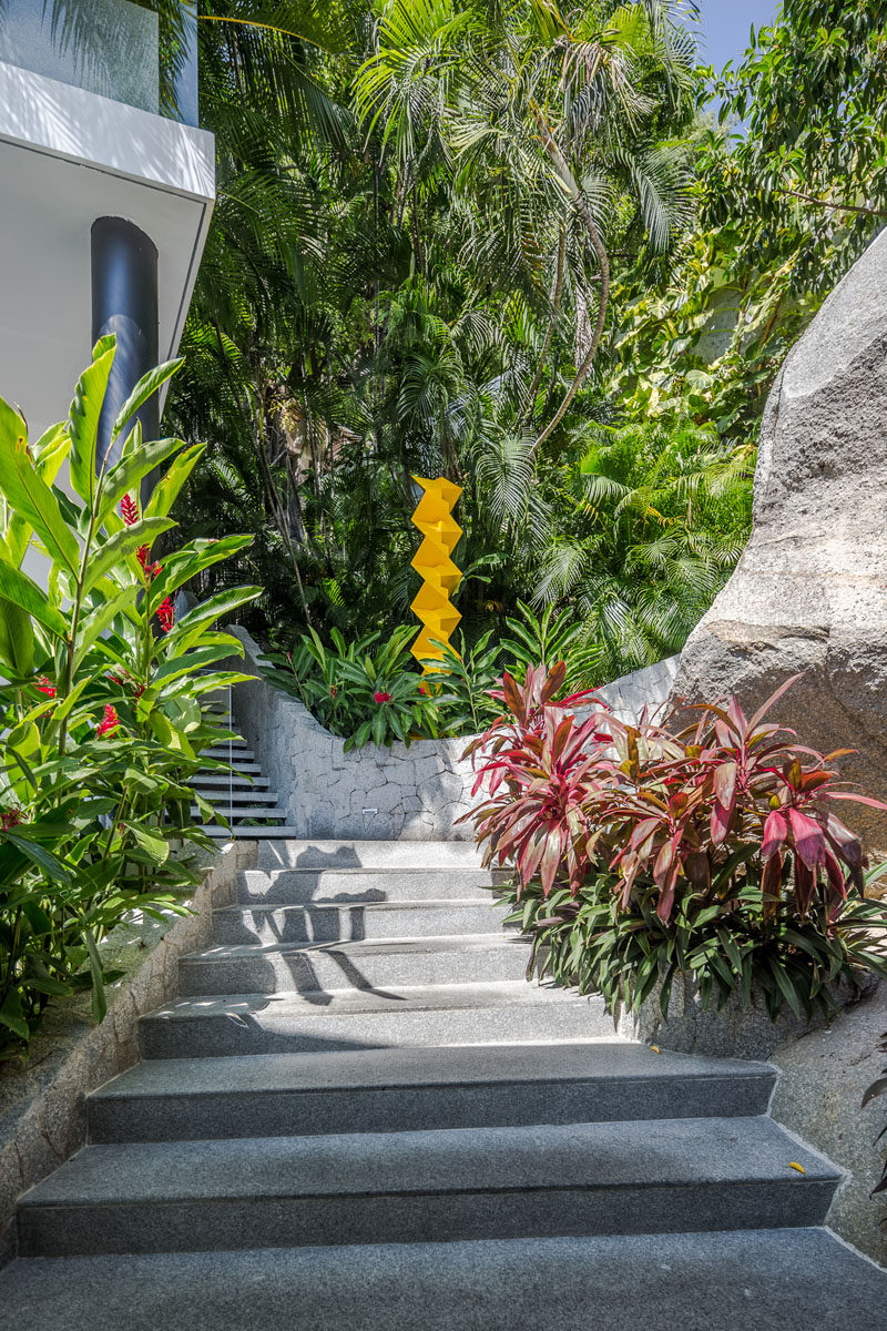 Stairs surrounded by lush landscaping connect the various areas of this modern house. #ExteriorStairs #ModernLandscaping #OutdoorStairs