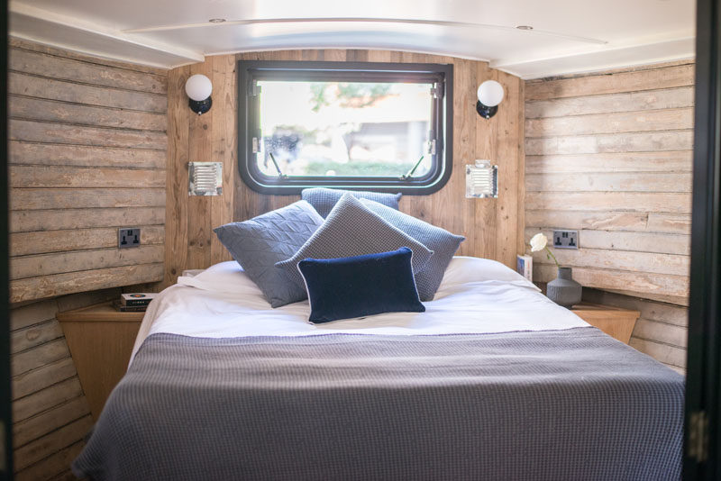 In the bedroom of a modern boathouse in London, built-in tables are positioned either side of the bed, while a window makes the room feel open. #Bedroom #ReclaimedWood #Boathouse