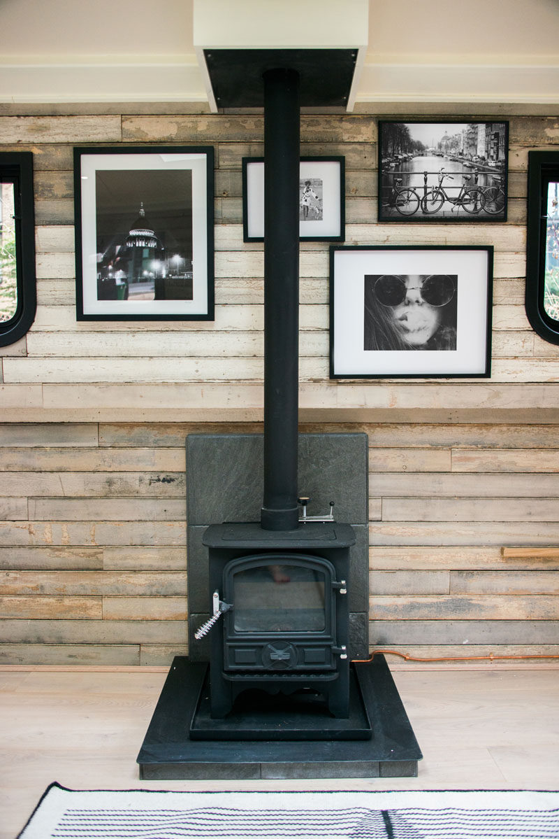 A wood burning fireplace helps to keep the living spaces of this modern boathouse warm and cozy. #Fireplace #WoodBurningFireplace