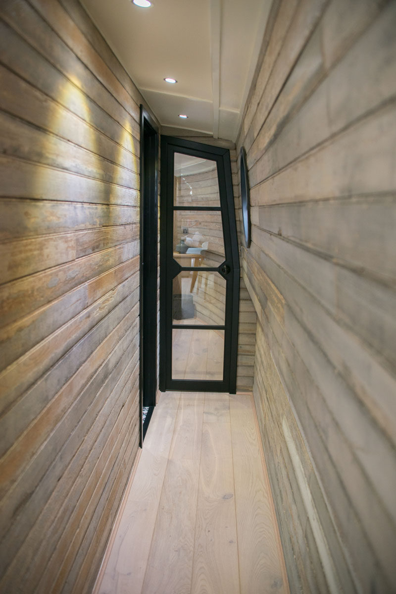 In this modern boathouse, a narrow wood-lined hallway leads to the bedroom and bathroom. #ReclaimedWood #WoodHallway #BlackFramedDoor